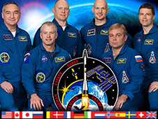 The Expedition 40 crew with their mission patch against a dark background of Earth with the sun on its horizon