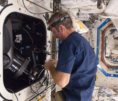 Canadian Space Agency astronaut Chris Hadfield sets up the ISS SERVIR Environmental Research and Visualization System (ISERV) in the Destiny laboratory of the International Space Station.