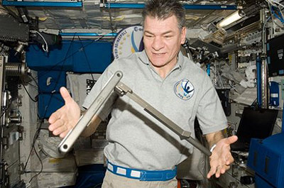 European Space Agency astronaut Paolo Nespoli observes a can crusher, built by students in HUNCH Program, during Expedition 26 aboard the International Space Station.