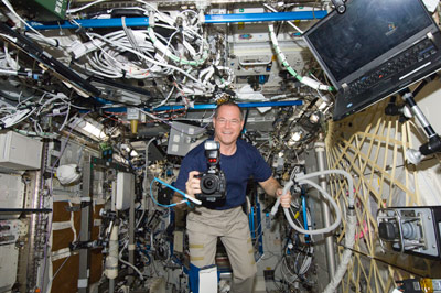 On Oct. 26, 2012, NASA astronaut Kevin Ford smiles for a photo while holding a still camera in the Destiny laboratory of the International Space Station.