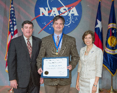 Matthew McCollum, center, electromagnetic effects subsystem manager supporting the ISS at Marshall, receives the 2013 Exceptional Service Medal award from NASA Johnson Space Center Director Ellen Ochoa, right, and Johnson Deputy Director Kirk Shireman.