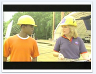 A student in a hard hat talks with a woman wearing a hard hat