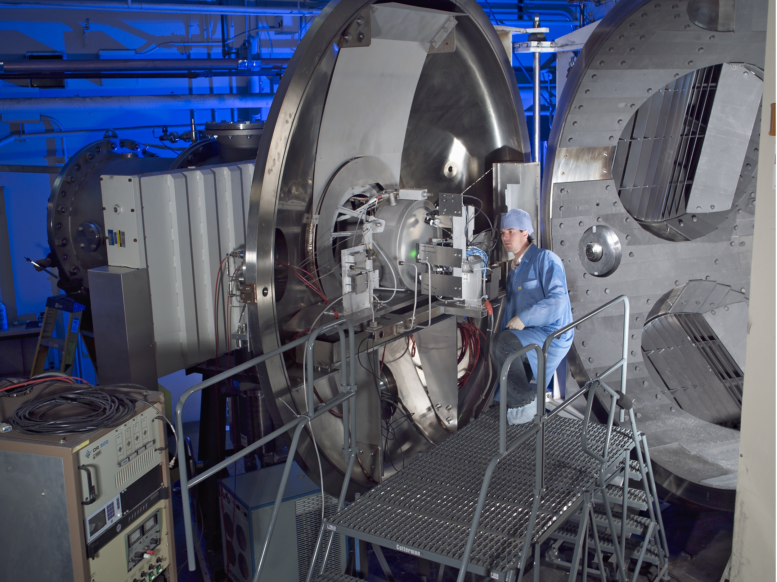An engineer at NASA Glenn checks the alignment of a camera system for the NEXT Long Duration Test prior to closing the vacuum facility back in 2005. The cameras take high-quality images of critical thruster components to track how these components erode with time. Image Credit: NASA