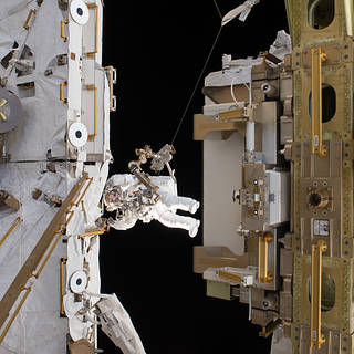 Astronaut in spacesuit at work outside space station with modules at either side of frame