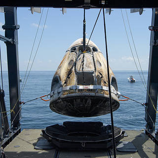 SpaceX Crew Dragon Endeavour spacecraft is lifted onto the SpaceX GO Navigator recovery ship shortly after it landed