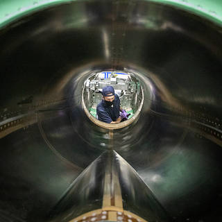 A technician works on the engine inlet of NASA's X-59 Quiet Supersonic Technology