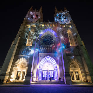 The facade of the Washington National Cathedral at nightfall with celestial galaxy projected on bricks in brilliant reds & blues