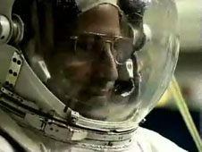 An astronaut wears a space suit helmet