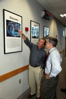 Shuttle Launch Director Mike Leinbach points out a new shuttle poster to Center Director Bob Cabana