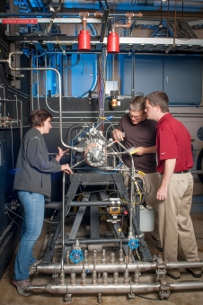 Technicians inspect the rocket injector assembly.