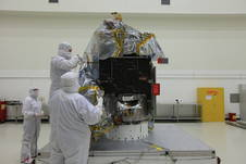 Workers remove the plastic cover from NOAA's Deep Space Climate Observatory spacecraft