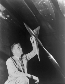 Richard T. Whitcomb examines a model designed in accordance with his transonic area rule in the 8-ft High-Speed Tunnel.