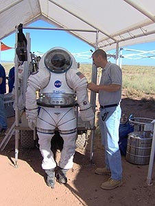 Carek standing next to a spacesuit under a tent in the desert