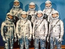 The Mercury Seven astronauts wearing silver-colored spacesuits