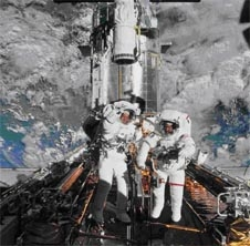 Two astronauts in white suits standing outside on the shuttle in space wave to the cameraman inside the space shuttle