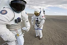 Two people in spacesuits stand on sandy ground