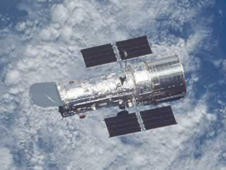 A view of the top side of Hubble high above Earth, with a bank of clouds obscuring Earth's surface