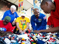 Three students and two adults play with LEGO bricks
