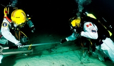 NEEMO 15 Commander Shannon Walker (NASA) and fellow aquanaut David Saint-Jacques (Canadian Space Agency) use a small telescoping boom as a means of translating across a simulated asteroid surface.