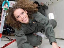 Tamra George floats inside an airplane during a microgravity flight
