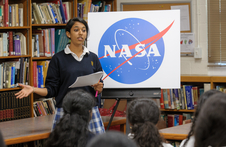 A Presentation High student introduces the speakers in front of a NASA logo.