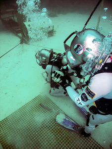 Aquanauts Steve Squyres and Tim Peake check equipment prior to exploring the 'asteroid' work site during training week 2012.
