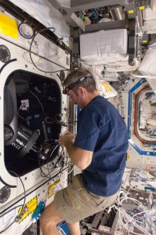 Canadian Space Agency astronaut Chris Hadfield sets up the ISS SERVIR Environmental Research and Visualization System (ISERV) in the Destiny laboratory of the International Space Station