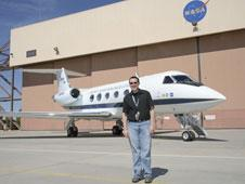 NASA engineer Ethan Baumann standing in front of the Gulfstream GIII testbed aircraft.