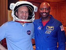 Paulo Oemig wears a space helmet while posing with Leland Melvin