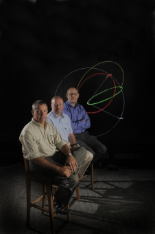 three guys sit in front of a graphic with dramatic lighting