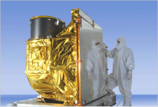 spacecraft intsrument in gold foil and man in white suit