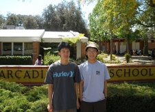 Jason Jong and Ziang Xie standing in front of their school.