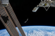 A set of CubeSats is photographed by an Expedition 38 crew member after deployment by the NanoRacks Launcher attached to the end of the Japanese robotic arm.