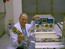 Dr. Dennis Morrison poses with the Microencapsulation Electrostatic Processing System flight hardware that was used on the International Space Station to produce microcapsules for cancer treatment delivery.