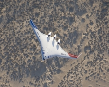 The X-48B Blended Wing Body aircraft banks over Mojave Desert scrub during the aircraft's fifth flight, on Aug. 14, 2007, from NASA's Dryden Flight Research Center.
