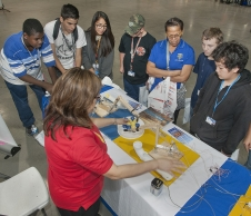 NASA Dryden's informal education manager Cecilia Cordova demonstrates how to operate a hands-on hydraulic robot arm educational tool to a team of students at the 2013 Salute to Youth.