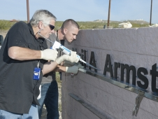 Don Whitfield and his son Kyle, both of whom work in NASA Armstrong's fabrication shop, add final touches to the center's new marquee at the intersection of Rosamond Boulevard and Lilly Avenue at Edwards Air Force Base.