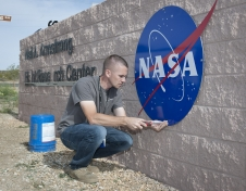 Kyle Whitfield screws in the four bolts holding the familiar NASA logo on the center's sign at Rosamond Boulevard and Lilly Avenue on the base.