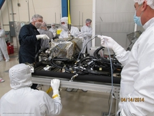 engineers in protective suits surround a table with wires and hardware