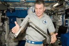 European Space Agency astronaut Paolo Nespoli observes a can crusher, built by students in the High school students United with NASA to Create Hardware (HUNCH) Program, during Expedition 26 aboard the International Space Station.