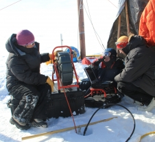 researchers surround a bore hole drilled in Greenland ice