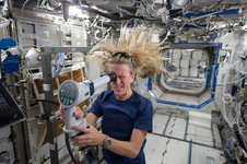 A crewmember uses a fundoscope to take still and video images of her eye while in orbit.