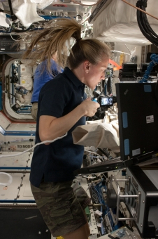 NASA astronaut Karen Nyberg works with new test samples for the Advanced Colloids Experiment-1, installed in the Light Microscopy Module (LMM) inside the Fluids Integrated Rack (FIR).