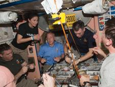 Expedition 26 and STS-133 crew members share a meal in the Unity node of the International Space Station.