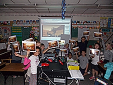 A classroom of students holding up a lithograph of the Curiosity rover