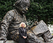 Melinda Higgins poses in front of a statue of Albert Einstein