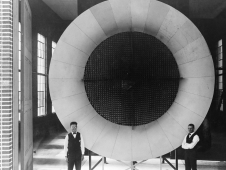Two mechanics standing in front of the first wind tunnel at the NACA's Langley Memorial Aeronautical Laboratory.