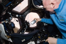 Expedition 30 Flight Engineer Andre Kuipers of the European Space Agency performs experiments using NanoRacks Smart Phone in the Cupola module