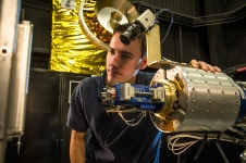 RROxiTT lead roboticist Alex Janas stands with the Oxidizer Nozzle Tool as he examines the work site.