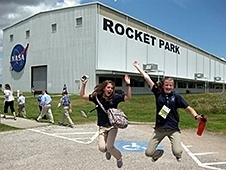 A picture of two students jumping into the air in front of a building with the words Rocket Park on the side